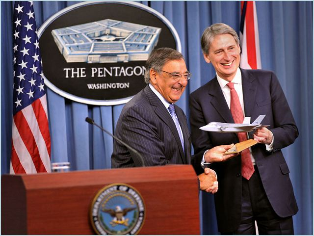 US Secretary of Defense Leon Panetta hands over a model of the F-35 Lightning II to UK Defence Secretary Philip Hammond at the Pentagon yesterday, 18 July, symbolically marking today's delivery of the first Lightning II jet to British forces